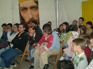 Un grupo de personas viendo el video en la carpa.